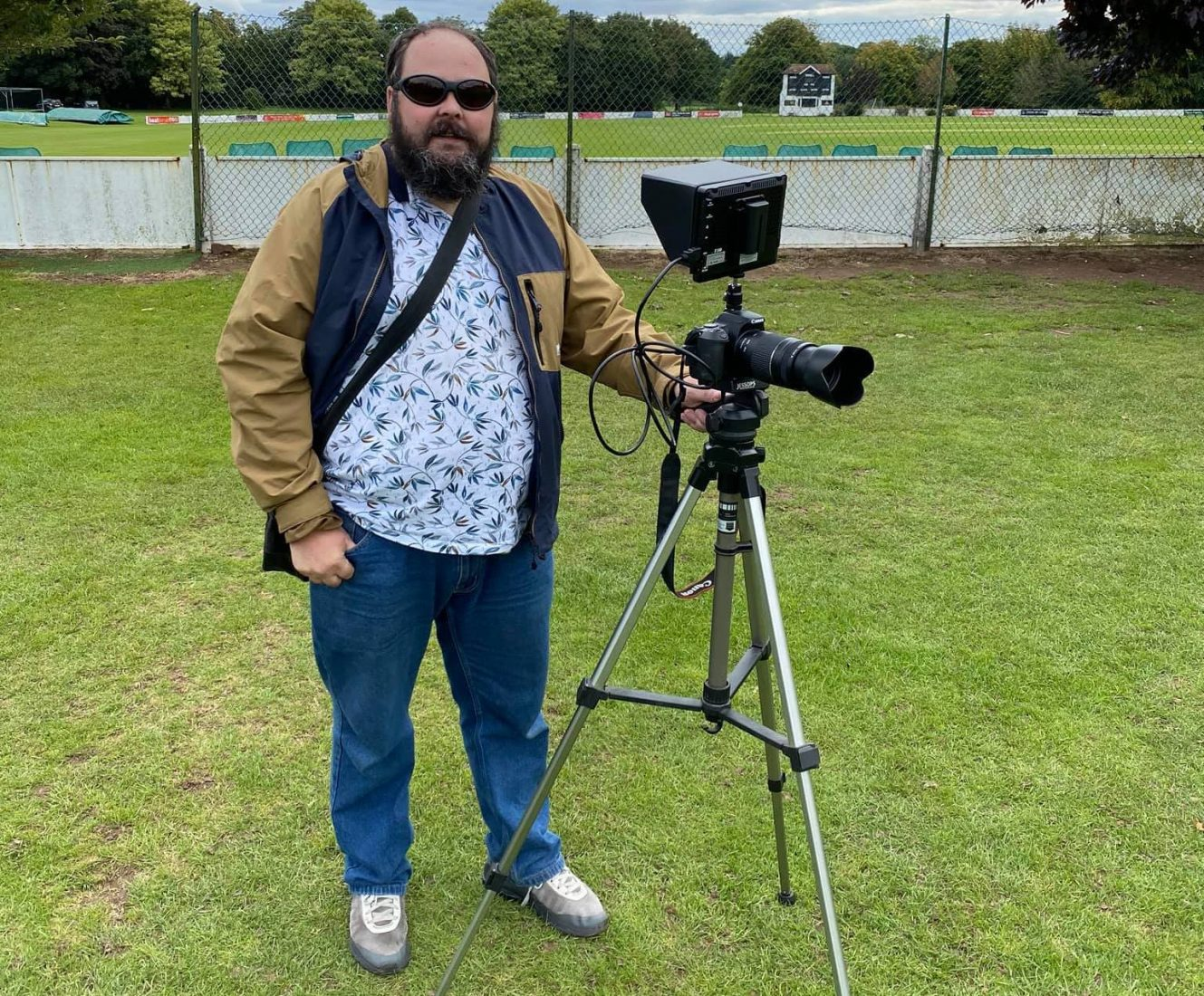 Steve, an SVI member is pictured standing with the hand on his camera and tripod in front of a cricket pitch. It's clear the camera has adjustments to help take photographs with a visual impairment.