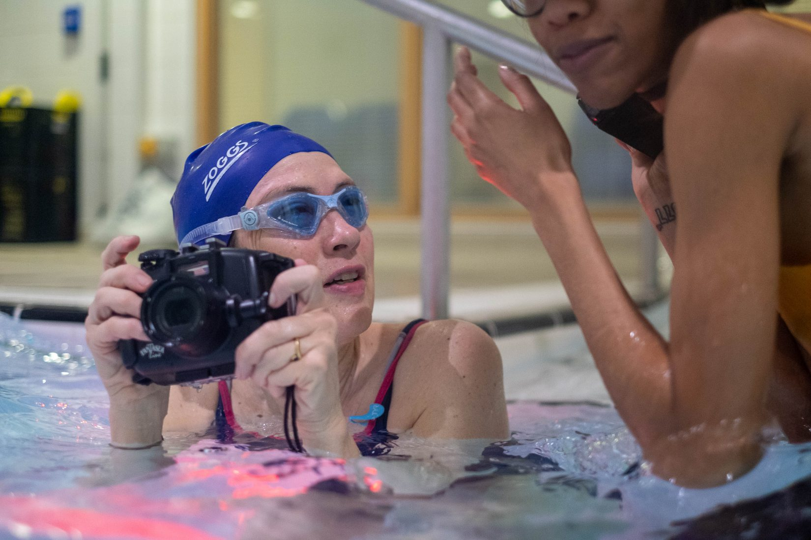 A woman wearing a swimming cap and goggles is in a pool, holding a camera in both hands just above the water. She looks at the woman beside her in the pool.
