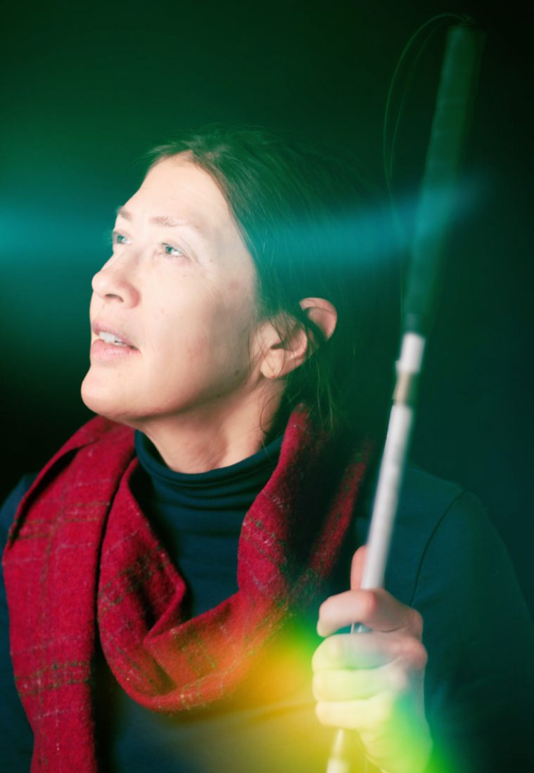 A woman in profile holding a white cane. Bright light flashes across her face, a translucent rainbow stripe across her hand.