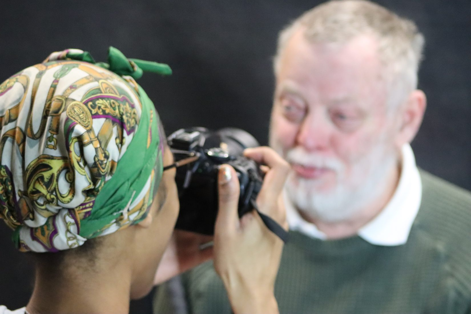 Woman in foreground with a colourful headscarf photographs a man with a grey hair and beard in front of a dark studio backdrop.