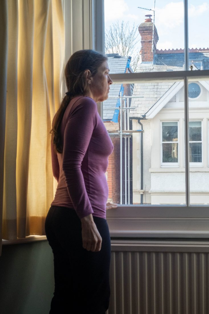 A woman in a pink top stands at an upstairs sash window looking out onto the street. The opposite house is in bright sunlight.