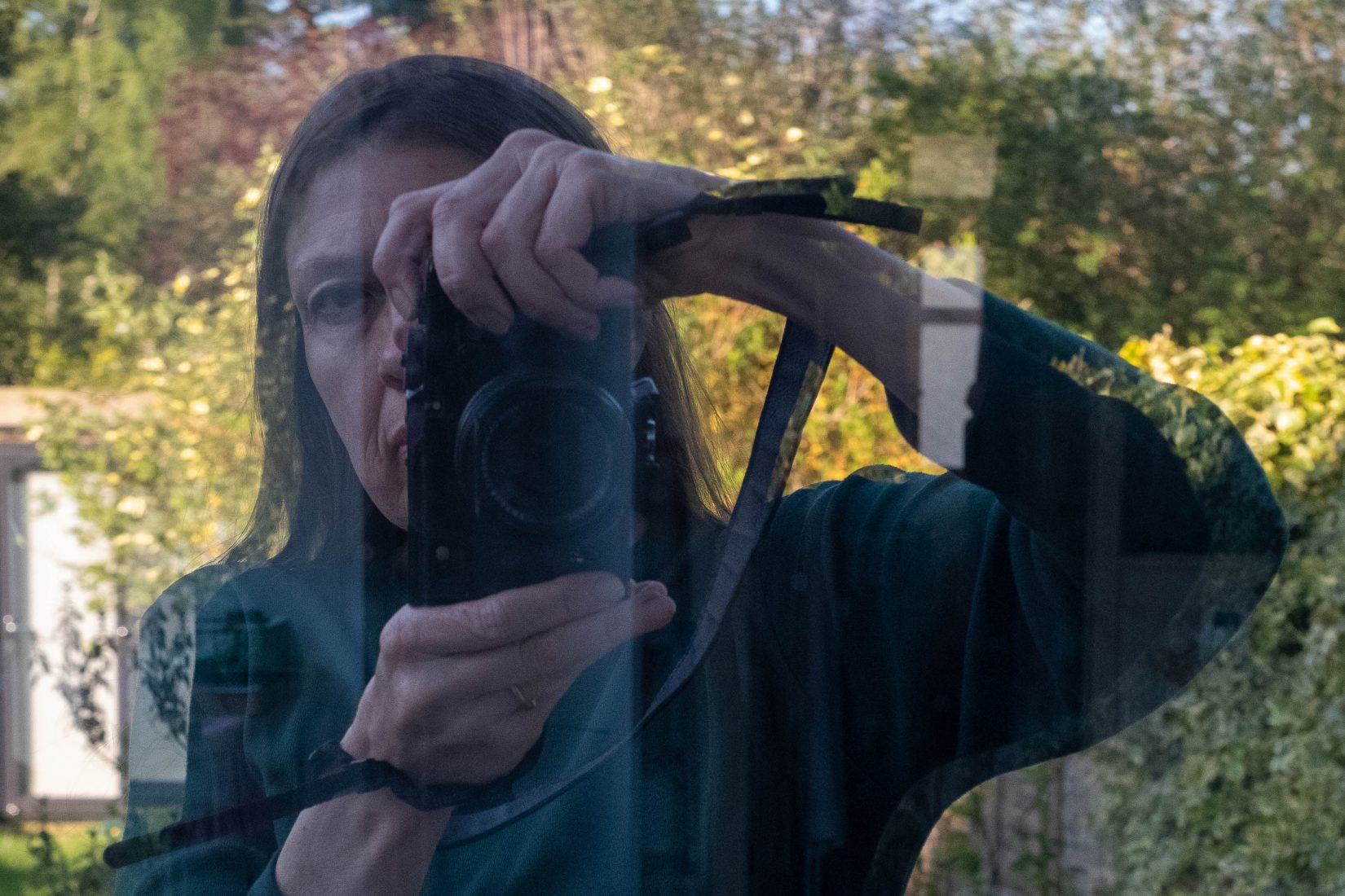 Reflection in a window of a woman holding a camera, obscuring half her face. Behind her is a brightly lit garden.