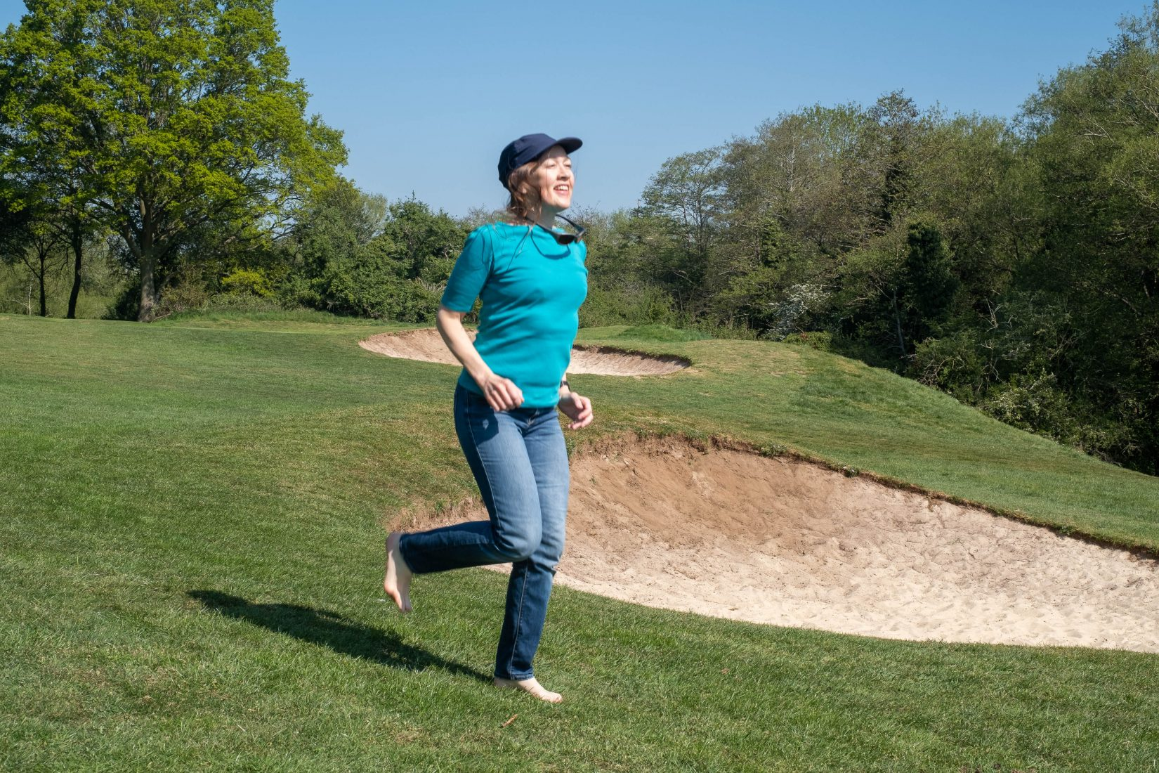 A woman runs barefoot on a manicured golf course with a look of joy on her face. Sunglasses on a strap bob around her neck.