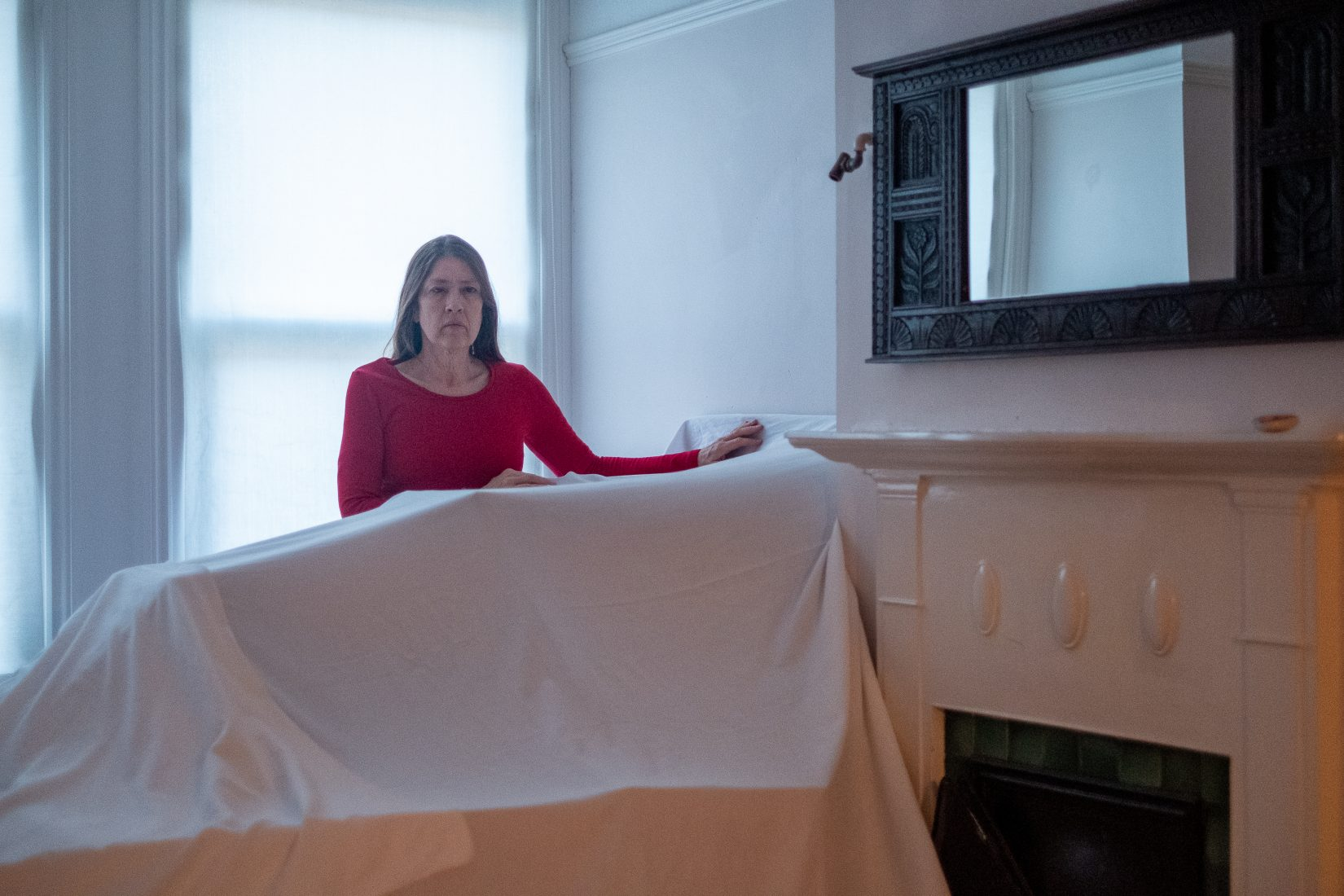 A woman in a red top stands behind furniture covered by a white sheet in a bright room