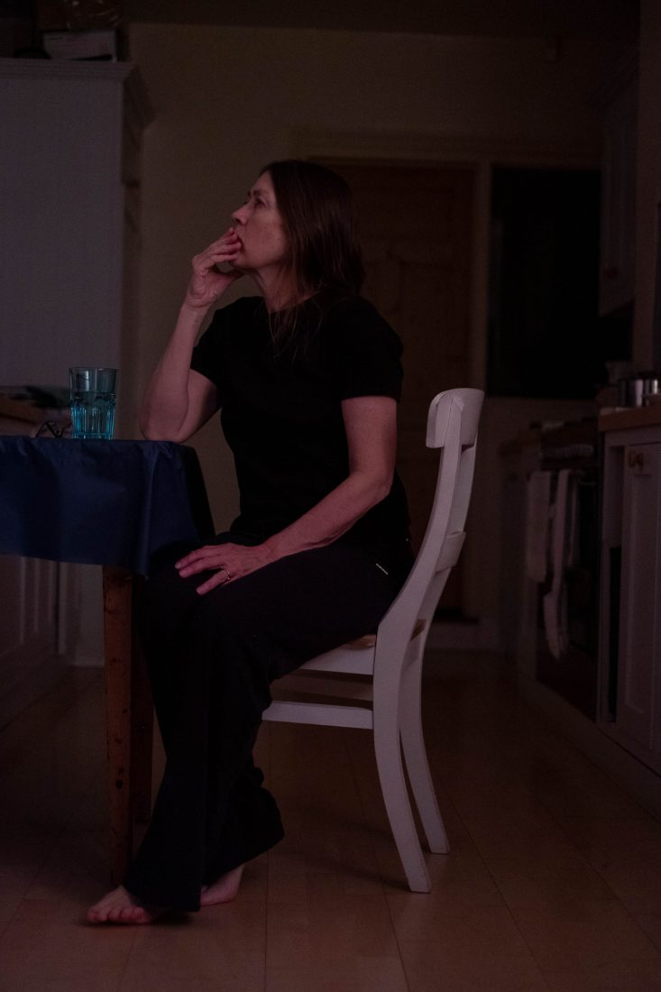 A woman in dark clothes sits at a kitchen table in a dark room, gazing upwards as if lost in thought.