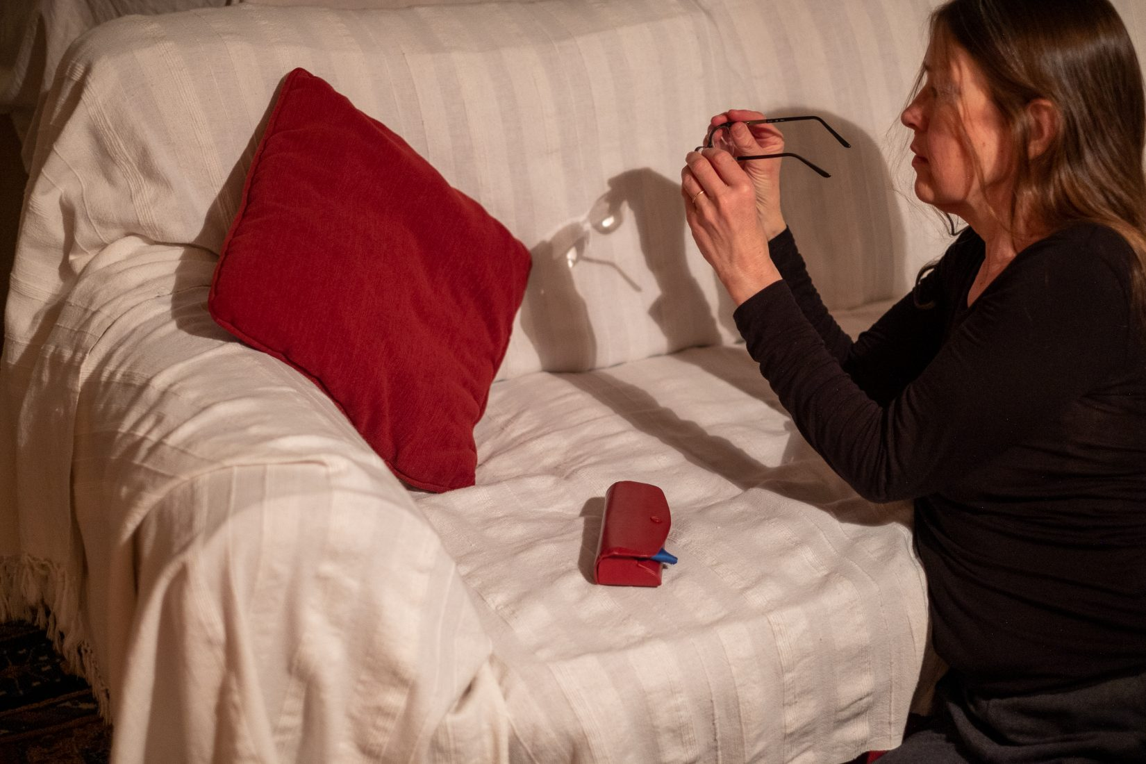 A woman kneels in front of a cream sofa holding out her bifocal glasses to create a strong shadow on the sofa.